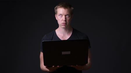 frustrado : Young handsome man with laptop against black background