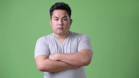 crossed : Young handsome overweight Asian man against green background