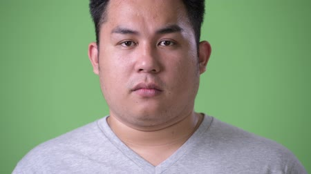 moudrý : Young handsome overweight Asian man against green background