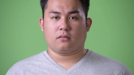 bilge : Young handsome overweight Asian man against green background