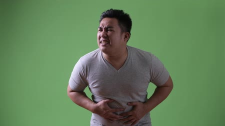nadváha : Young handsome overweight Asian man against green background
