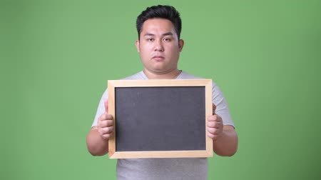 tablica : Young handsome overweight Asian man against green background