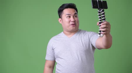 tripod shot : Young handsome overweight Asian man against green background
