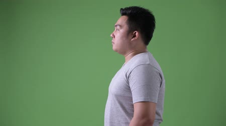 плечо : Young handsome overweight Asian man against green background