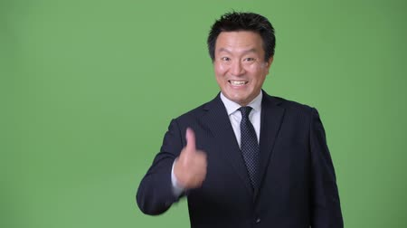 kciuk w górę : Mature Japanese businessman against green background