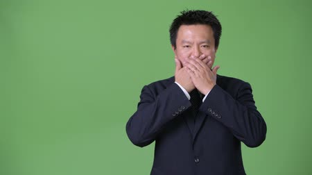bilge : Mature Japanese businessman against green background