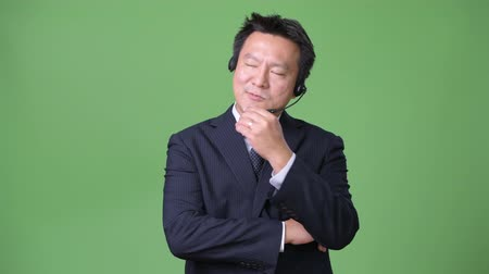 телемаркетинг : Mature Japanese businessman against green background