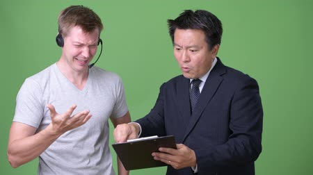 телемаркетинг : Mature Japanese businessman and young Scandinavian man worker together