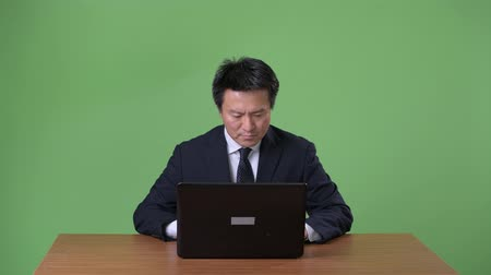laptop screen : Mature Japanese businessman against green background