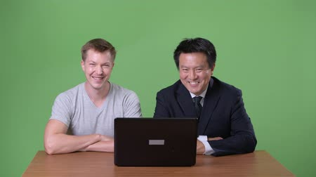 crossed arms : Mature Japanese businessman and young Scandinavian man worker together
