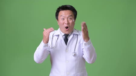 raising fist : Mature Japanese man doctor against green background
