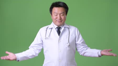 zavaros : Mature Japanese man doctor against green background