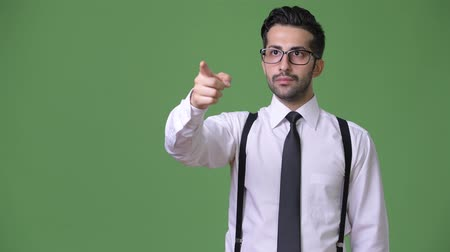 ближневосточный : Young handsome bearded Persian businessman against green background
