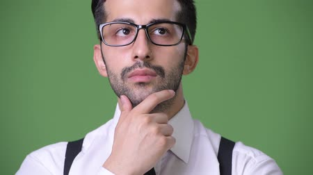 hand on chin : Young handsome bearded Persian businessman against green background