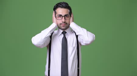 bölcs : Young handsome bearded Persian businessman against green background