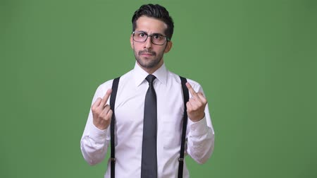 hand sign : Young handsome bearded Persian businessman against green background