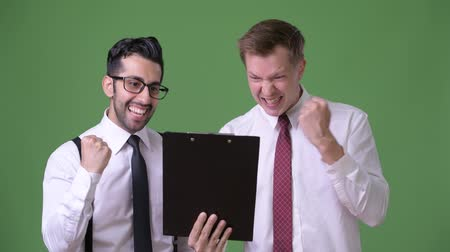 raising fist : Two young multi-ethnic businessmen working together against green background