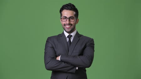 crossed : Young handsome bearded Persian businessman against green background
