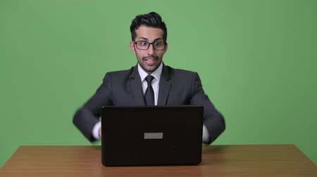 raising fist : Young handsome bearded Persian businessman against green background