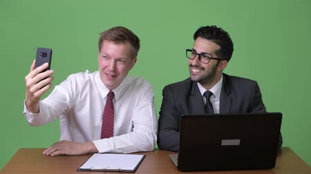 vlogging : Two young multi-ethnic businessmen working together against green background