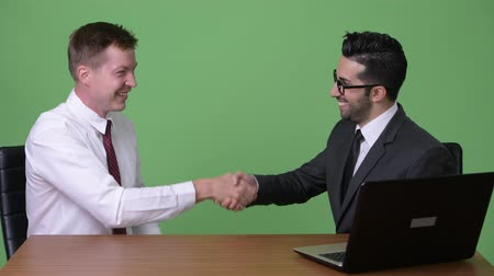 together trust : Two young multi-ethnic businessmen working together against green background