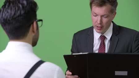 finnish : Two young multi-ethnic businessmen working together against green background