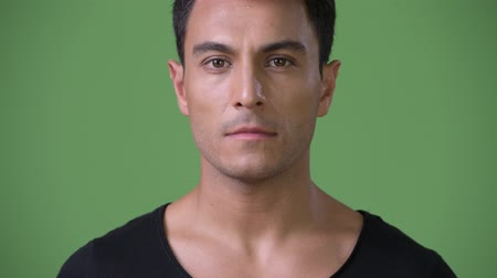 латино : Young handsome Hispanic man against green background Стоковые видеозаписи