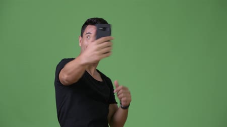 vlogging : Young handsome Hispanic man against green background Stock Footage