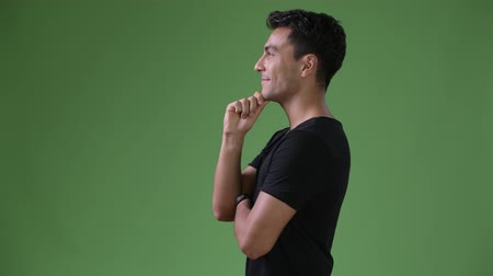 hand on chin : Young handsome Hispanic man against green background Stock Footage