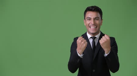 raising fist : Young handsome Hispanic businessman against green background