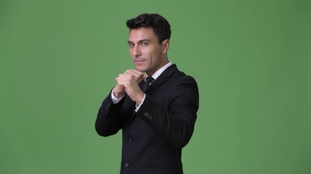 postura : Young handsome Hispanic businessman against green background