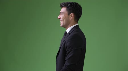 profil : Young handsome Hispanic businessman against green background