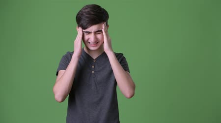 мигрень : Young handsome Iranian teenage boy against green background Стоковые видеозаписи