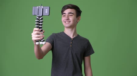 vlogging : Young handsome Iranian teenage boy against green background Stock Footage