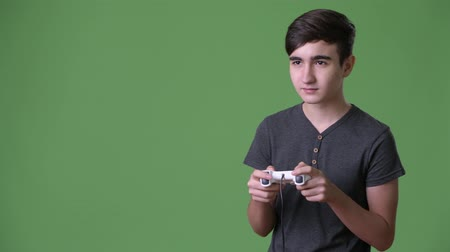 chroma key background : Young handsome Iranian teenage boy against green background Stock Footage