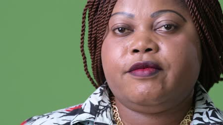braids : Overweight beautiful African woman against green background