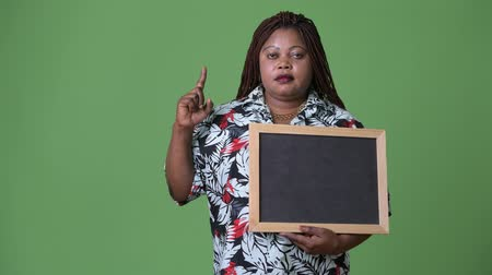 tablica : Overweight beautiful African woman against green background