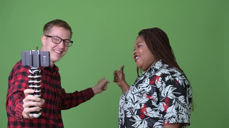 together trust : Overweight African woman and young Scandinavian man together against green background