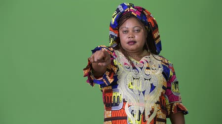 braids : Overweight beautiful African woman wearing traditional clothing against green background
