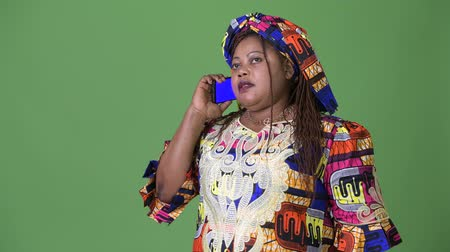 mulheres adultas meados : Overweight beautiful African woman wearing traditional clothing against green background