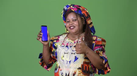 fonat : Overweight beautiful African woman wearing traditional clothing against green background
