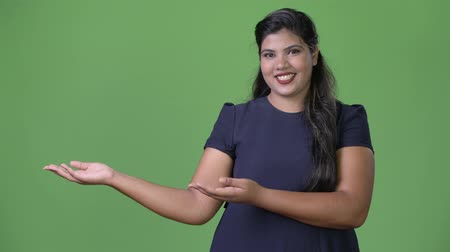 overweight : Young overweight beautiful Indian businesswoman against green background