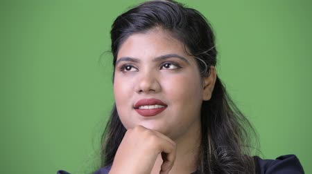 hand on chin : Young overweight beautiful Indian businesswoman against green background