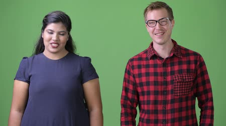 csapatmunka : Young multi-ethnic business couple together against green background