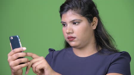 túlsúly : Young overweight beautiful Indian businesswoman against green background