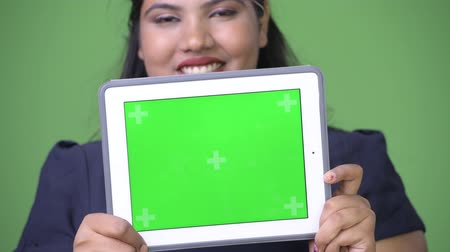 foco no primeiro plano : Young overweight beautiful Indian businesswoman against green background