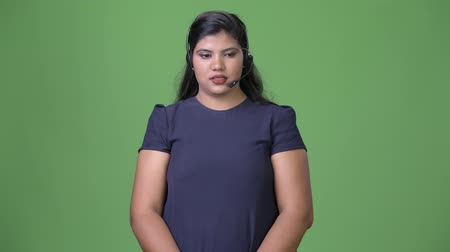 representante : Young overweight beautiful Indian businesswoman against green background