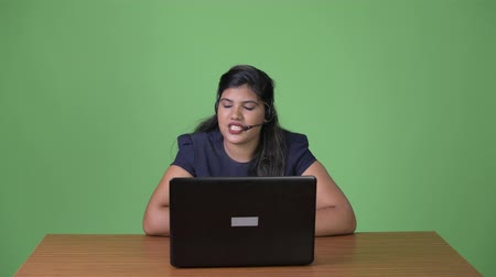 телемаркетинг : Young overweight beautiful Indian businesswoman against green background