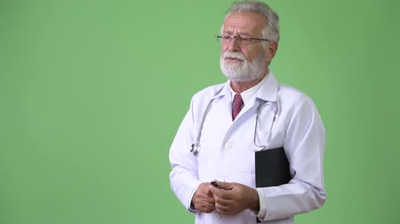 hand on chin : Handsome senior bearded man doctor against green background