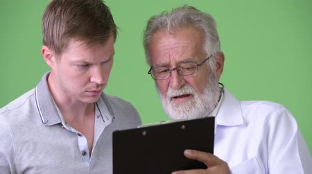 panoya : Senior bearded man doctor consulting man patient against green background
